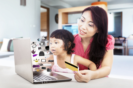 Happy mother and daughter shopping online with laptop at home photo