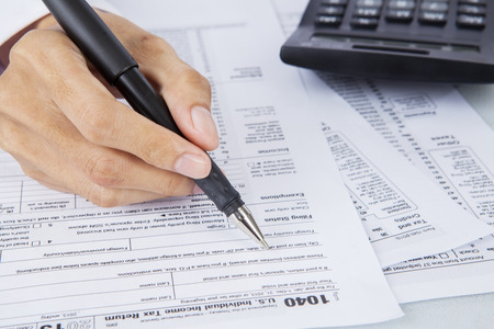filling out: Filling out income tax forms with calculator and pen