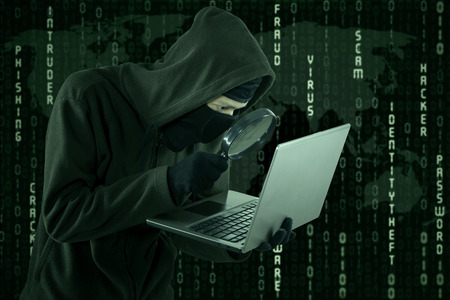 cyber business: Portrait of hacker looking for user information by using magnifying glass Stock Photo