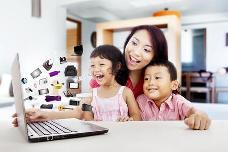 ラップトップ コンピューターを使用してオンライン ショッピング幸せのアジア家族が自宅で撮影