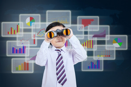 Little businessman see vision using binoculars in front of business futuristic background photo