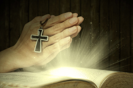 catholic symbols: Hands of man holding holy bible and rosary with magical rays coming out from the bible Stock Photo
