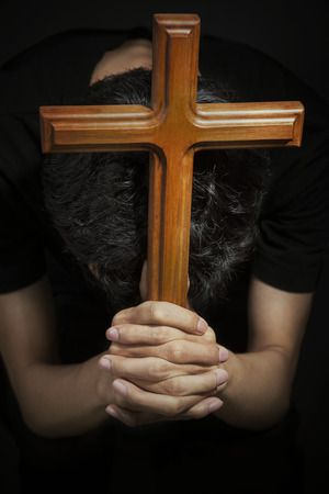 Close-up of male praying by holding wooden cross photo