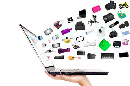 electronic store: Modern laptop in the hand with lots of merchandise isolated on white Stock Photo