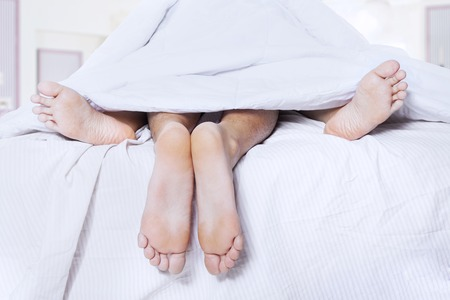 Close-up of couples feet having intimate relation in bed