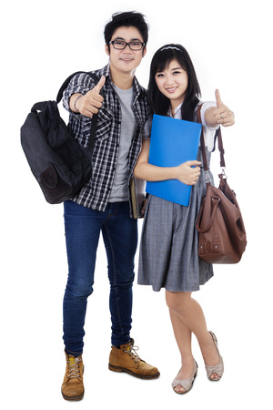 Happy trendy college students with bags and books, showing thumbs-up at camera, photo