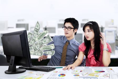 Shocked businesspeople working at office looking dollar note is coming out from computer screen photo