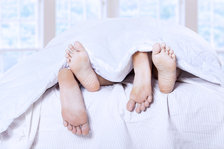 Close-up of couples feet having intimate relation in bed photo