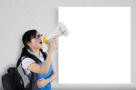 bawl: Portrait of a female student shouting via megaphone near to copyspace Stock Photo