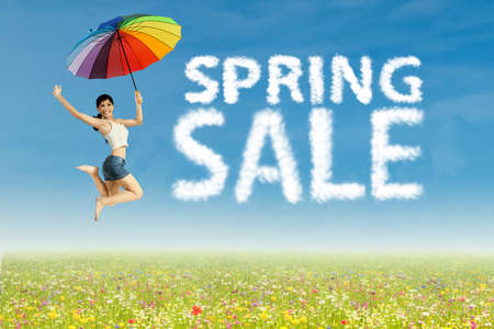 Young woman jumping with clouds shaped of spring sale photo