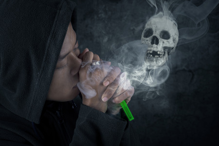 A young man smoking over a black background photo