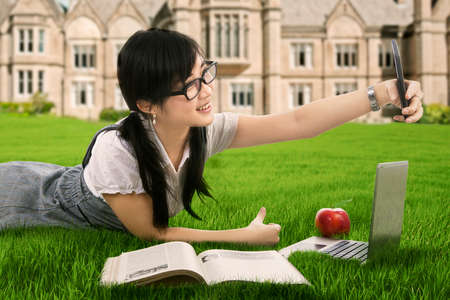 Cheerful female college student taking photo selfie while  lying on the green grass photo
