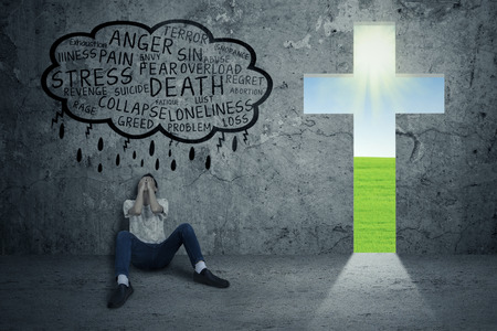 젊은 남자가 필사적으로 그 옆에 십자가 상징하는 예수와 함께 바닥에 앉아