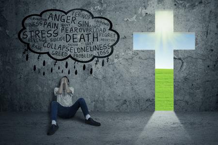 Jonge man wanhopige zittend op de vloer met een kruis symboliseert Jezus naast hem Stockfoto