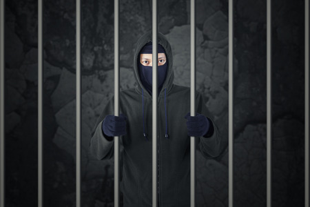 Behind bars. Arrested burglar in prison. Criminal with balaclava caught and arrested. Stock Photo