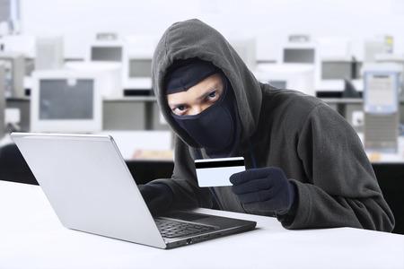 danger: Internet Furto - un uomo che indossa un passamontagna e in possesso di un po 'di carta di credito seduto dietro un computer portatile,