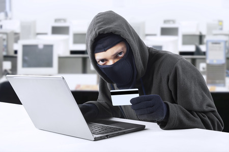 internet fraud: Internet Theft - a man wearing a balaclava and holding a credit card while sat behind a laptop,