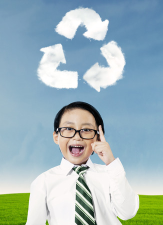 Happy boy pointing at recycle symbol above his head photo