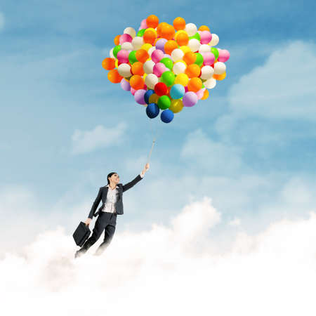 weather balloon: Young businesswoman holding colorful balloons and flying over clouds Stock Photo