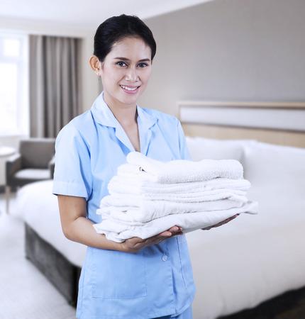 personal de limpieza: Señora sonriente joven con toallas de limpieza que disparan a la habitación del hotel Foto de archivo