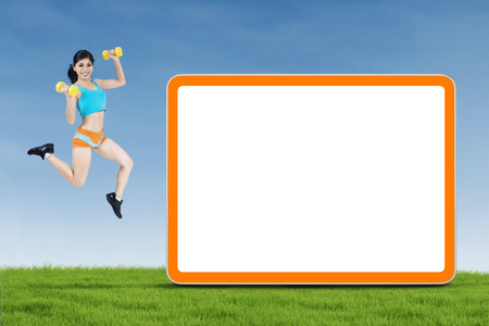 Happy fitness woman jumping with empty board on the meadow photo