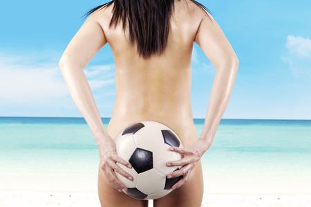 De la mujer atractiva de la parte trasera que sostiene un bal�n de f�tbol. disparar a la playa photo
