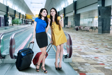 Two woman traveling with suitcase standing in airport photo