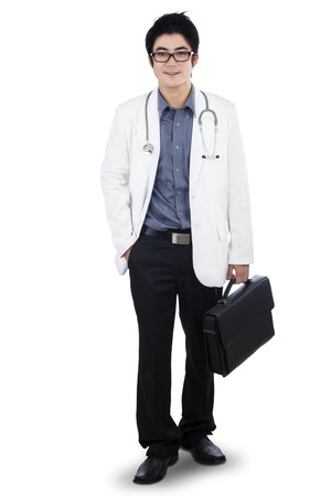 Portrait of medical doctor standing while holding briefcase. isolated on white background photo