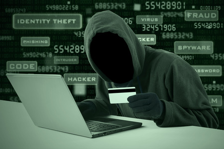 scammer: Internet Theft - a man wearing a balaclava and holding a credit card while sat behind a laptop,