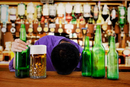alcoholic man: Drunk man sleeping in the bar, with bottle of beer in his hand
