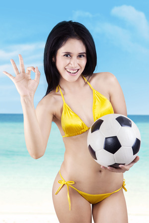 Young sexy woman with a soccer ball giving OK gesture photo
