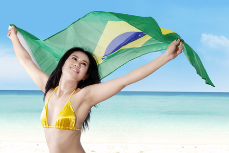 Beautiful young woman holding Brazil flag wearing bikini at beach photo