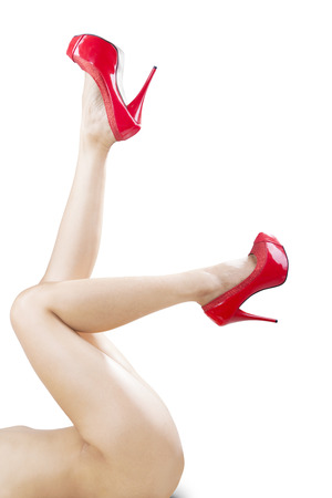Beautiful female legs with red high heels isolated on white background photo
