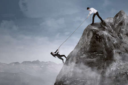 Portrait of businessman help his partner to climb the cliff by pulling her with a rope photo