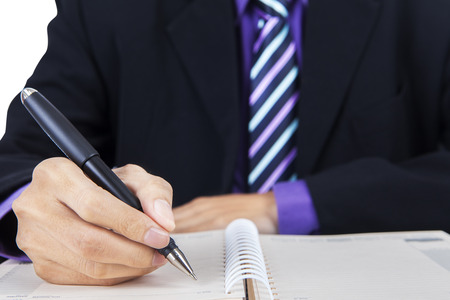 daily planner: Closeup of businessman recording of the work plan in the office