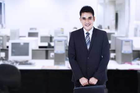 Asian businessman standing in office with briefcase photo