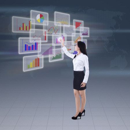 online trading: Success businesswoman presenting the different types of diagrams in virtual future interface