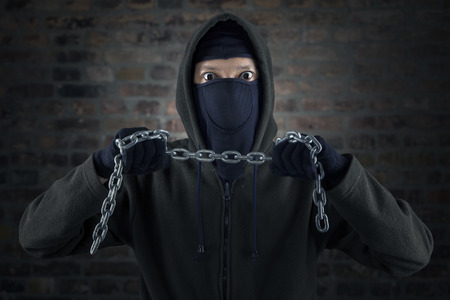 Dangerous murderer with chain standing in front of brick wall photo