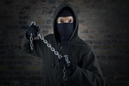 Portrait of killer holding chain in front of brick wall photo