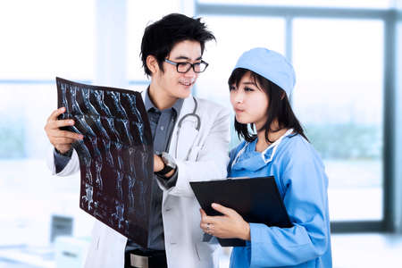 Male and female doctor looking at patient xray film photo