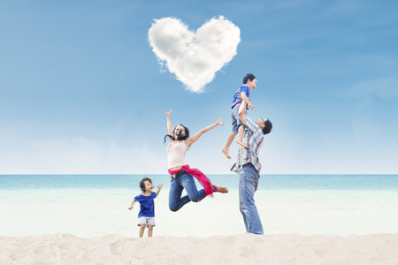 under heart: Happy family jumping under heart cloud at the beach