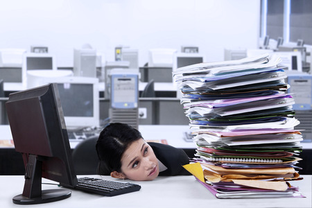 secretary woman: Portrait of overworked businesswoman looking at pile of documents