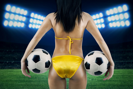 Womans Sexy Backside Holding a Soccer Ball. Shoot at soccer stadion photo