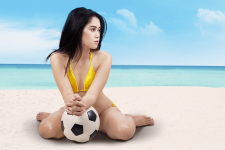 Portrait of sexy girl posing with ball sitting on the beach photo