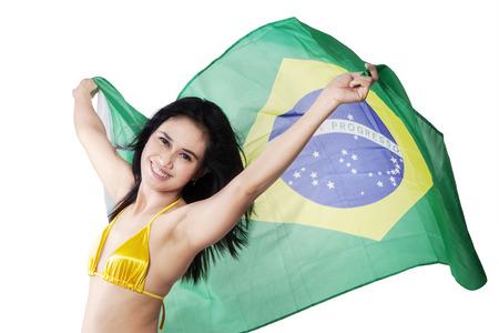 Beautiful young woman holding Brazil flag wearing bikini. isolated on white photo