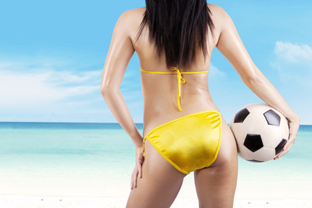 Backside sexy woman with a soccer ball at beach photo
