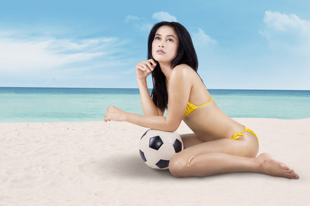 Young sexy woman with a soccer ball posing at the beach photo