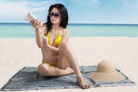 nude sexy girl: Beautiful young woman applying sunscreen sitting on beach in summer Stock Photo