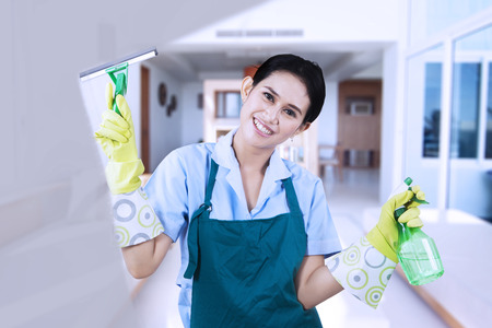 Smiling asian woman cleaning a window with glass cleaner Stock Photo