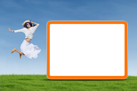 A young woman is jumping next to empty board on the green grass photo